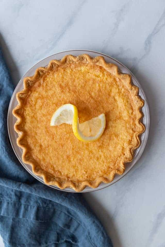 Overhead view of lemon chess pie with a lemon slice on top.