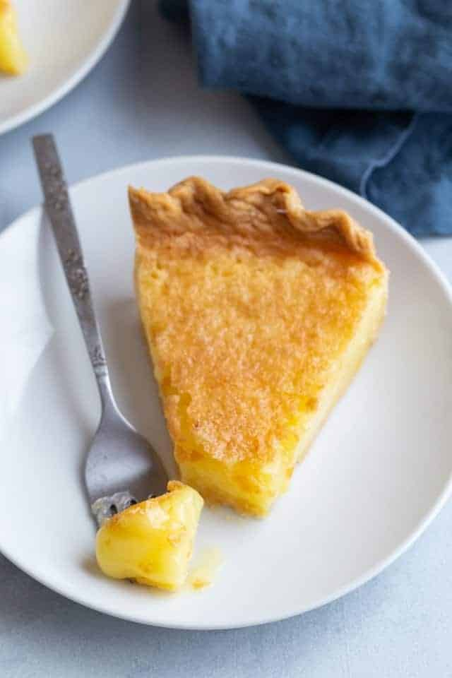 Angled view of a slice of lemon chess pie with a fork taking a bite out.