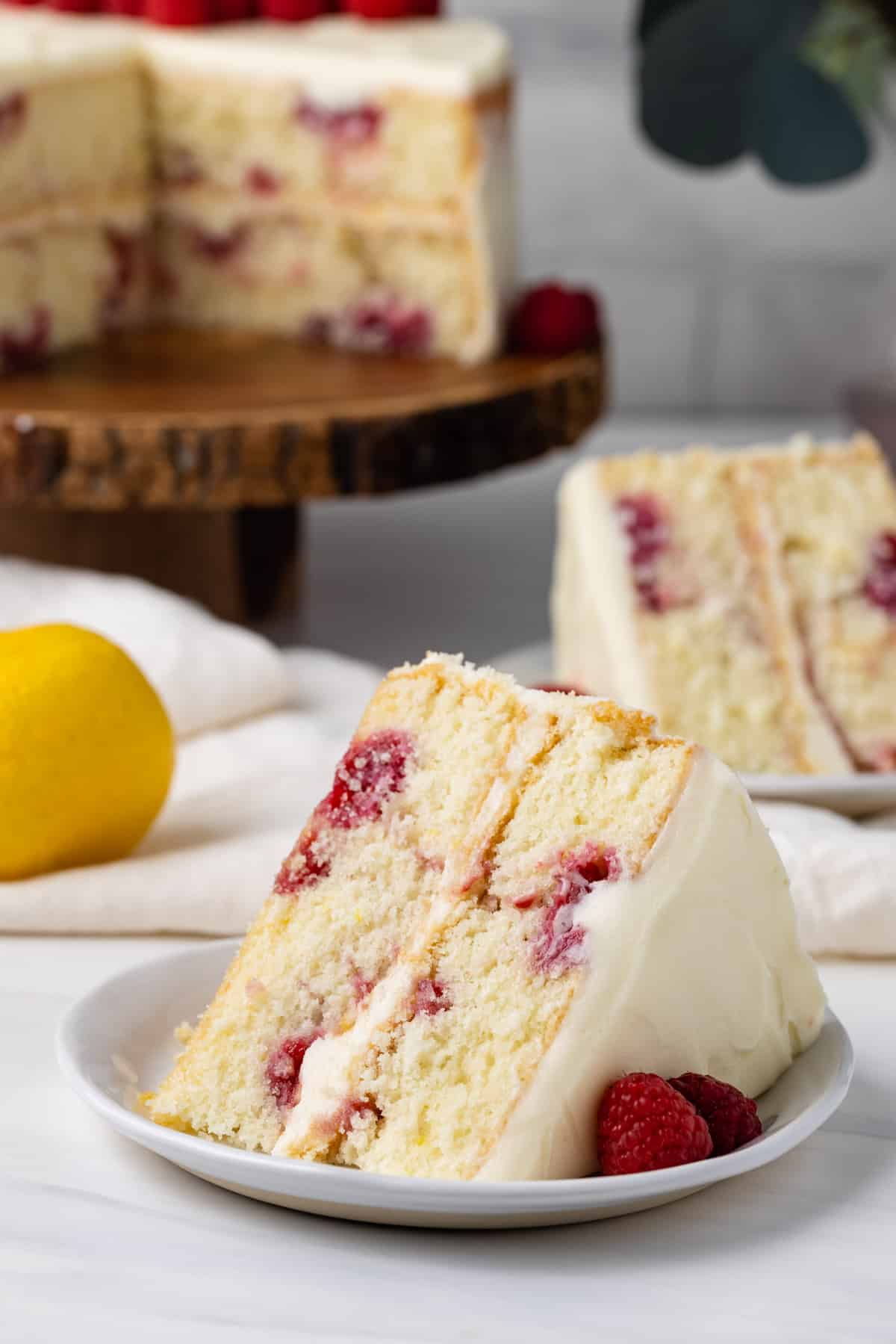 A slice of lemon raspberry cake on a plate in front of the lemon raspberry cake