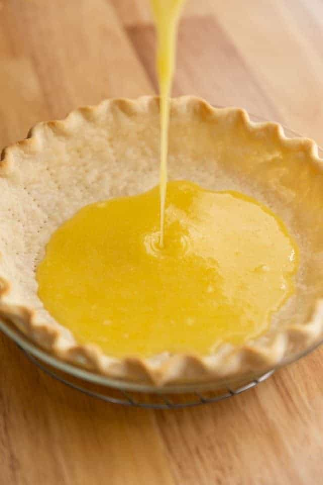 angled view of lemon filling being poured into a pie crust