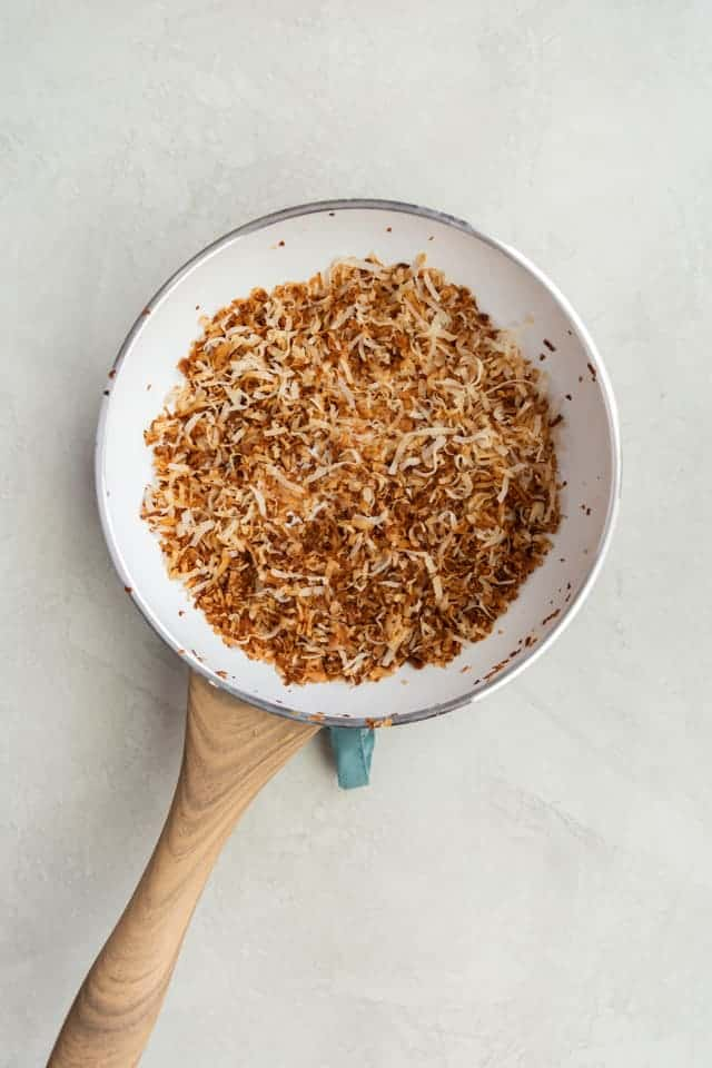 toasted coconut in a white fry pan