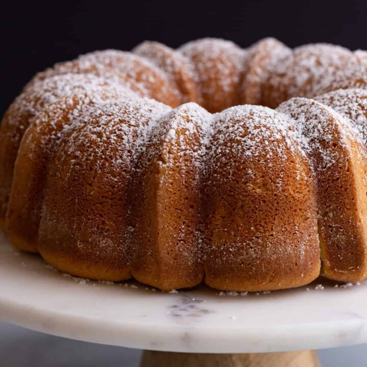 side view of sour cream pound cake on a cake stand