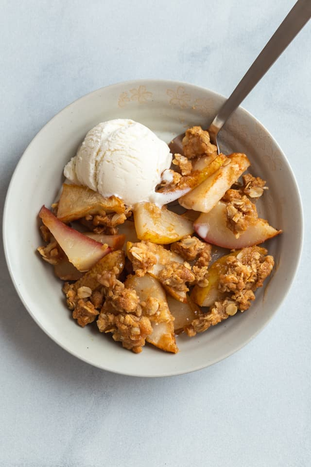 overhead view of pear crisp in a bowl with a scoop of ice cream