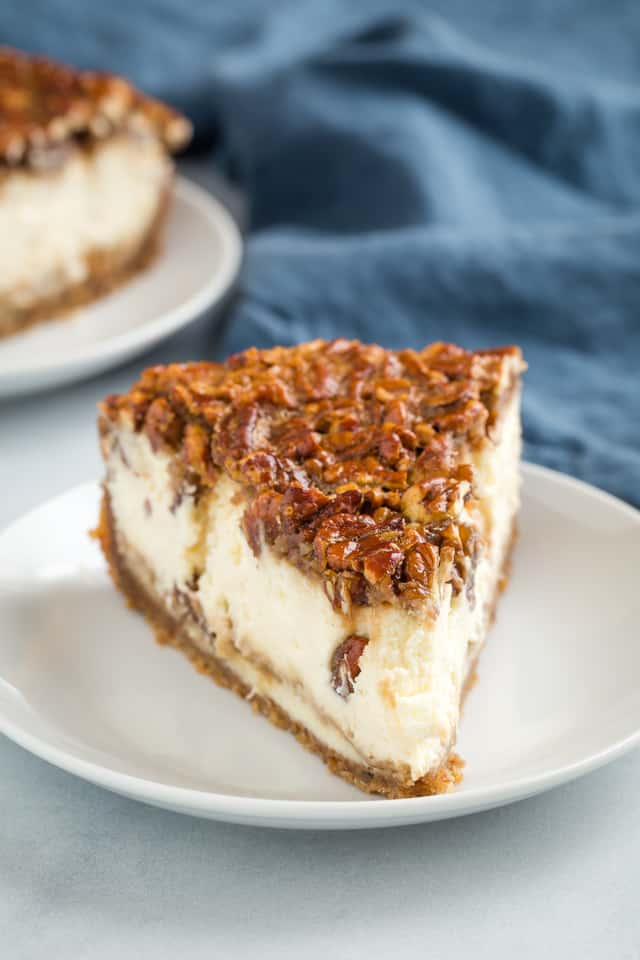front view of a slice of pecan pie cheesecake on a white plate