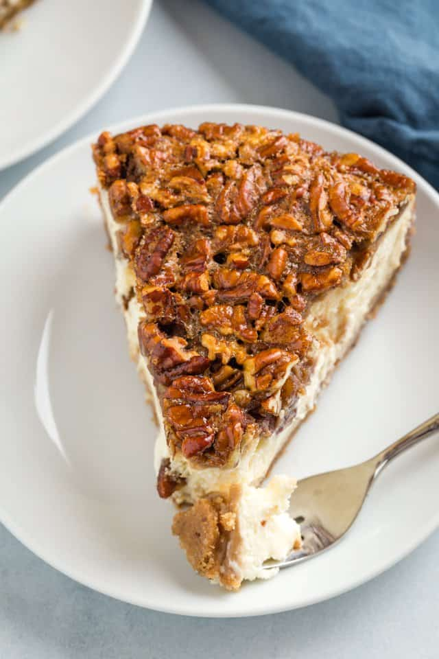 high angle view of pecan pie cheesecake with a fork taking a bite out