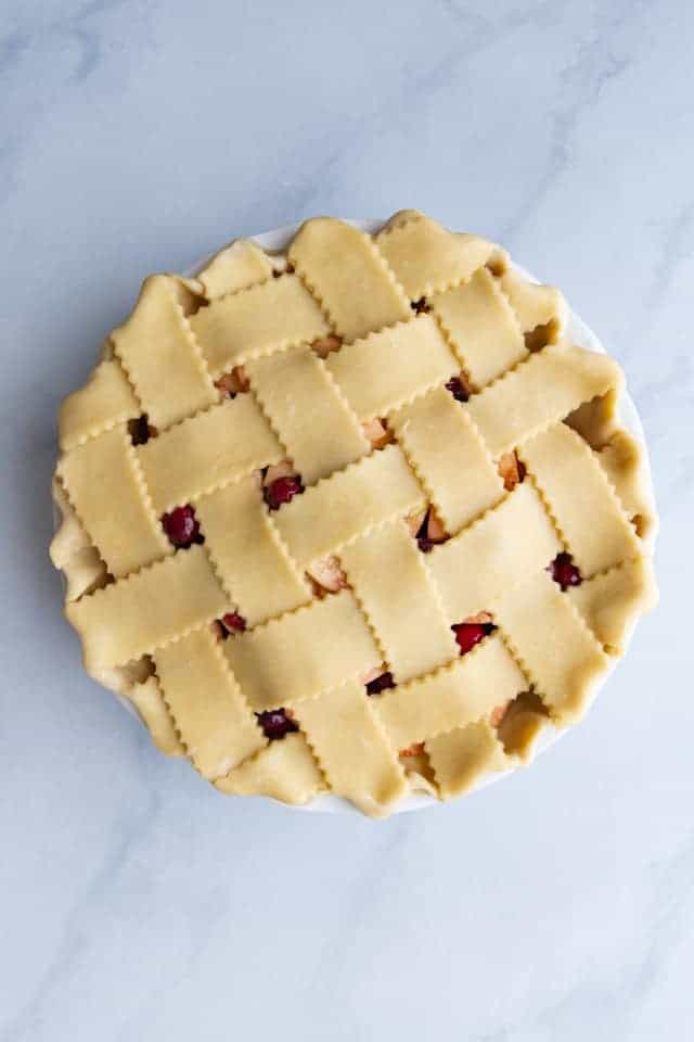 overhead view of an unbaked apple cranberry pie with a lattice crust