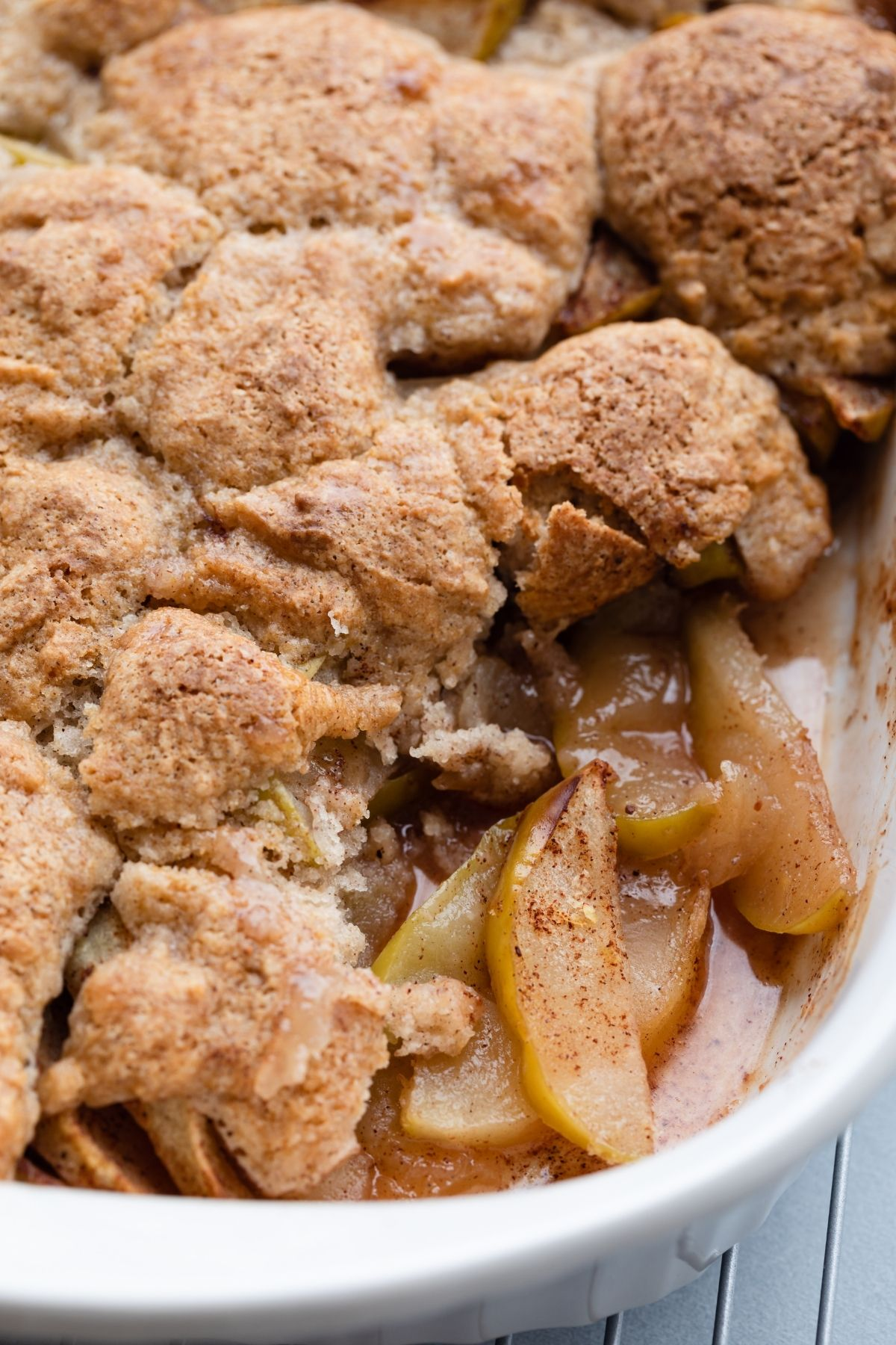 close up of a spoon scooping out apple cobbler
