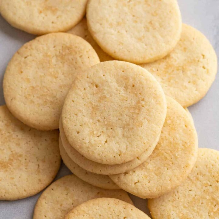 overhead view of basic butter cookies scattered on white parchment paper