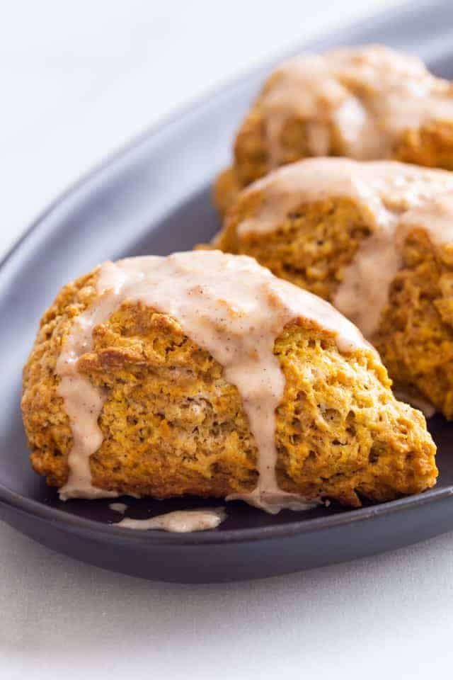 side view of pumpkin scones topped with spiced glaze on a dark blue plate