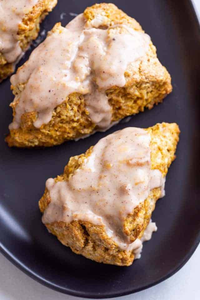 overhead view of pumpkin scones topped with spiced glaze on a dark blue plate