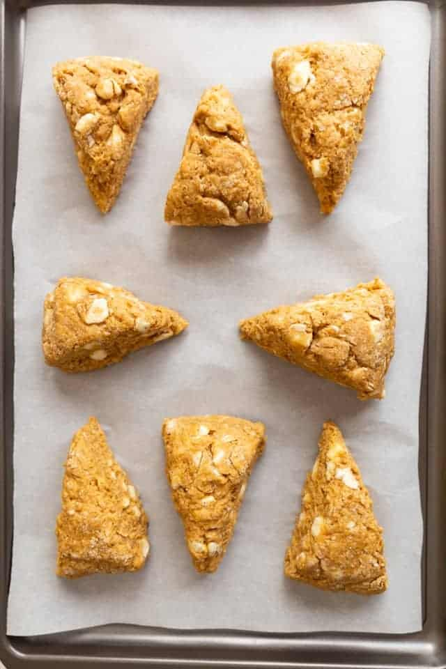 overhead view of unbaked pumpkin scones on a baking sheet