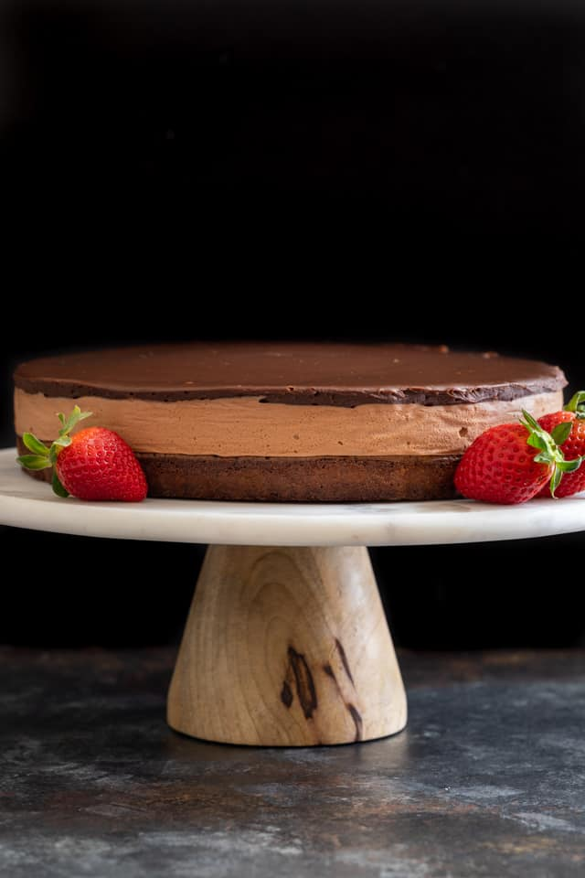 Triple Nutella mousse cake with strawberries on a cake stand.