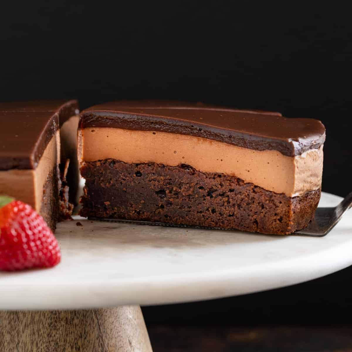Triple Nutella mousse cake on a cake plate with a slice being taken out.