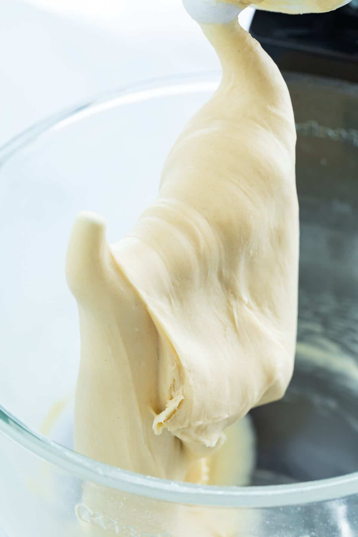 Homemade croissant dough on a dough hook of a stand mixer