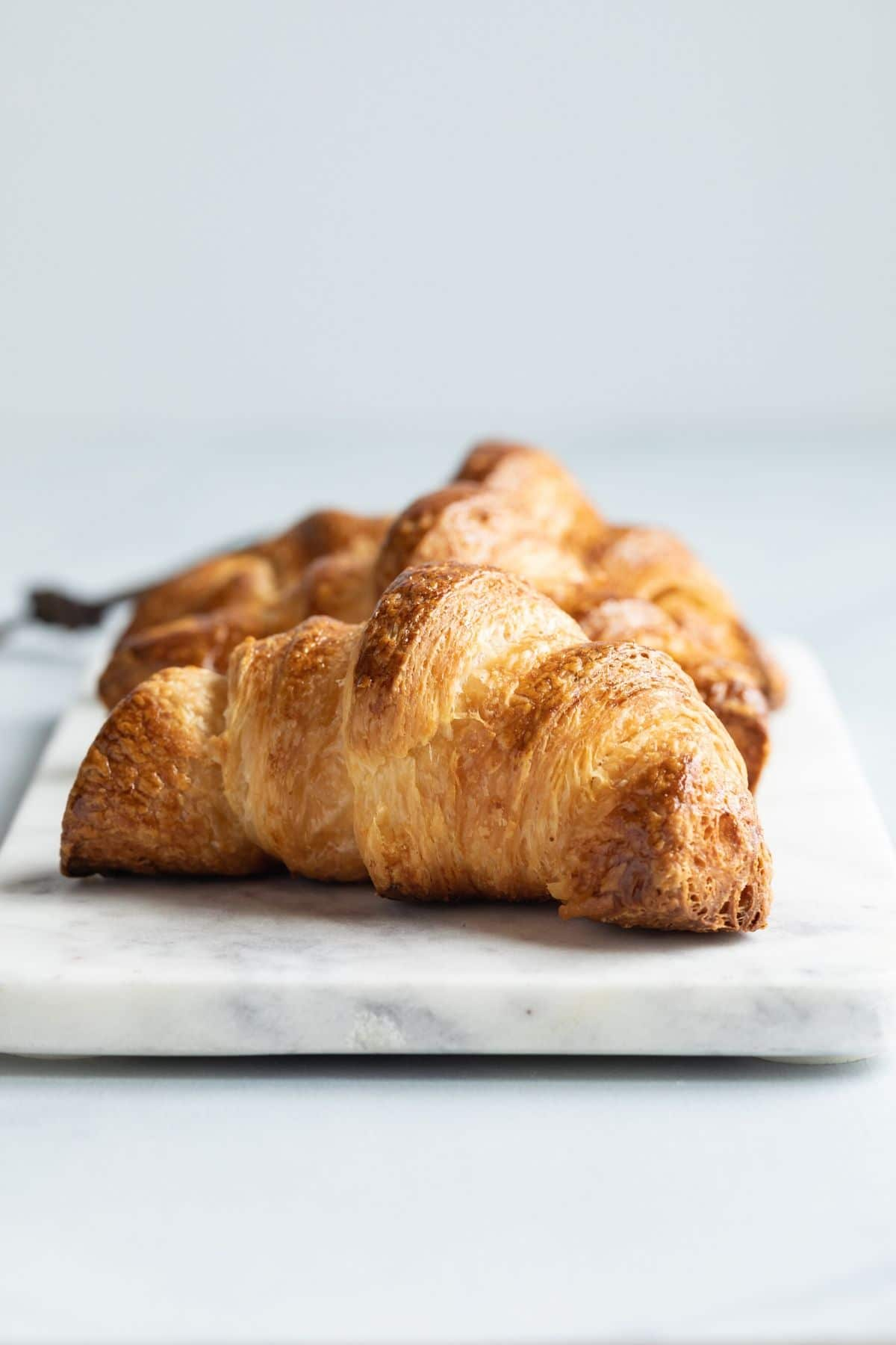 Front view of three croissants on a marble slab
