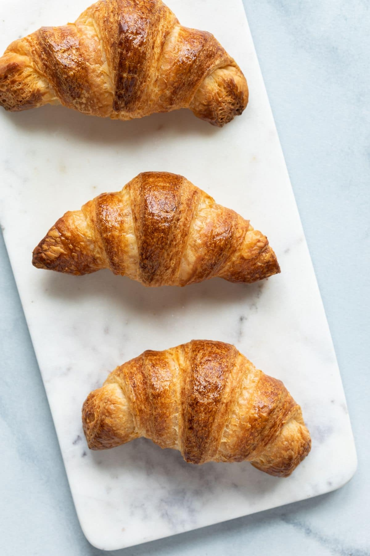 Overhead view of three croissants on a marble slab