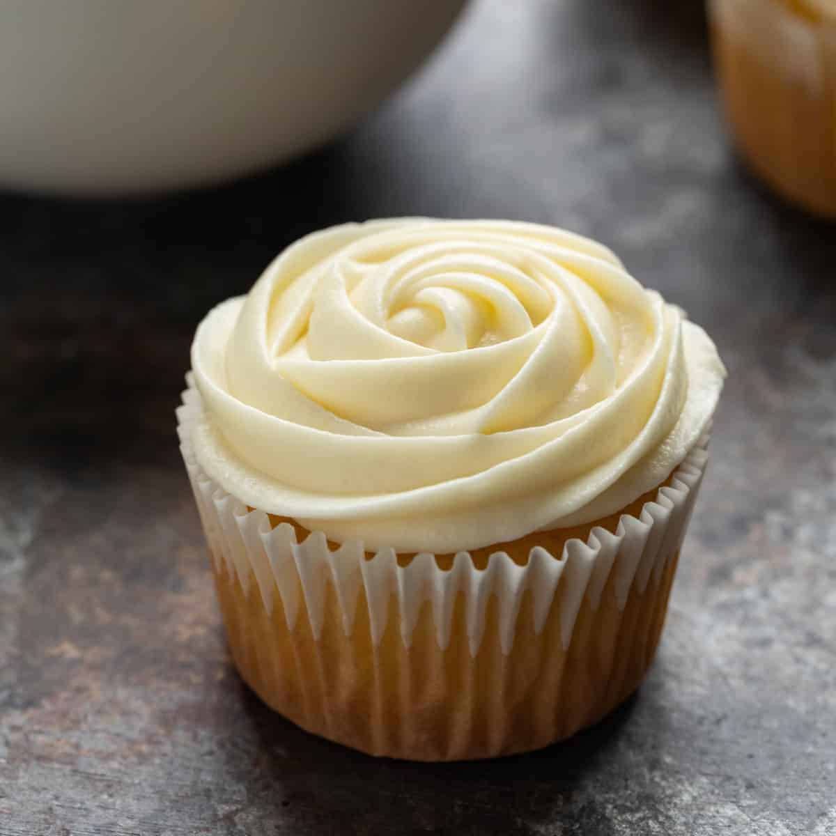 Side view of cream cheese frosting swirled over yellow cupcakes