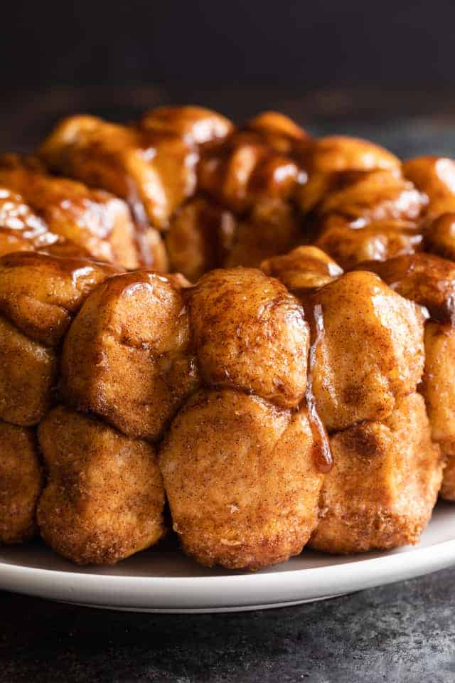 monkey bread on white plate with drippy caramel