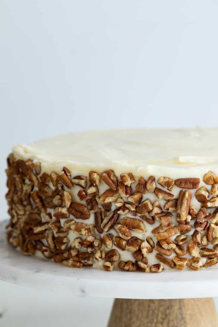 close up carrot cake dotted with pecans