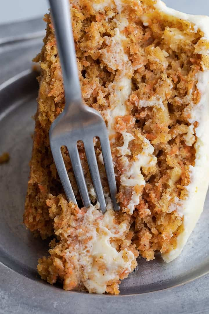 slice of pineapple carrot cake with a fork taking a bite out