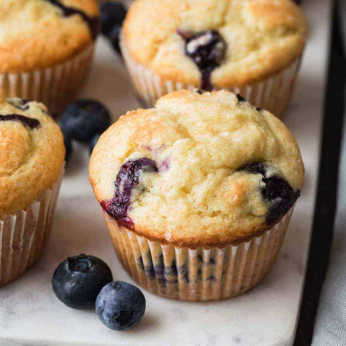 angled view of blueberry muffins on a marble board