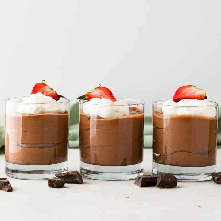 side view of classic French chocolate mousse in glass cups with whipped cream and strawberries