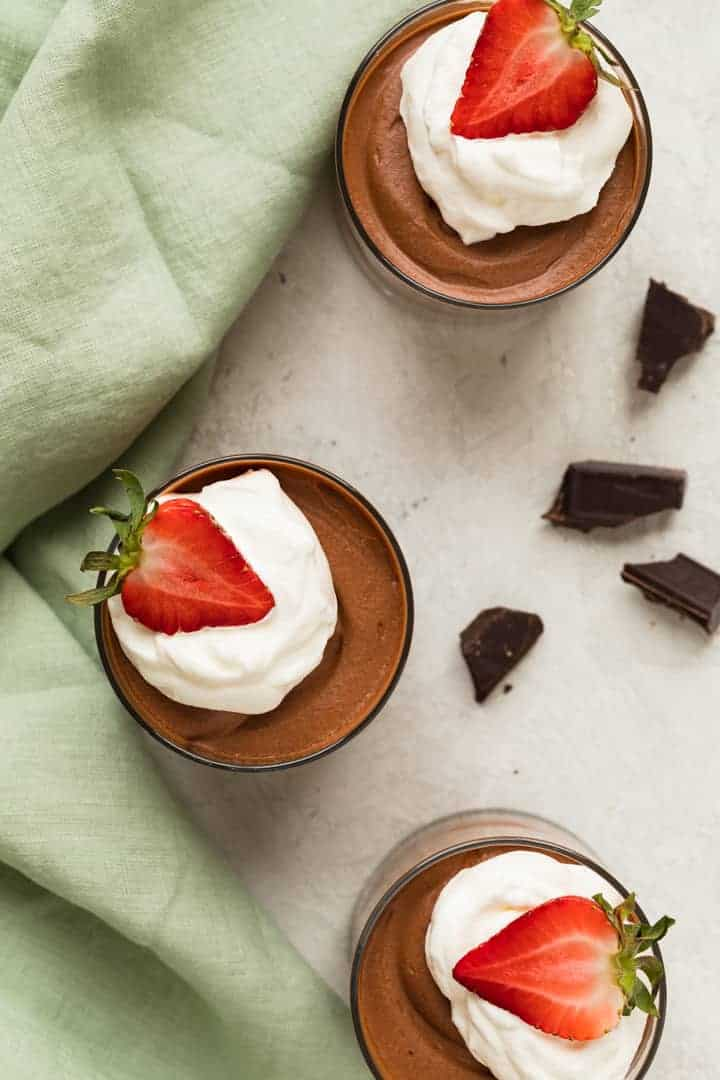 overhead of classic chocolate mousse with whipped cream and strawberries in glass cups