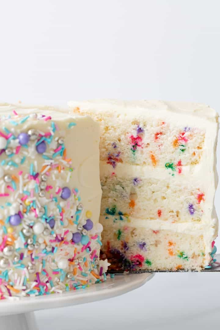 side view of slice of funfetti cake being taken out