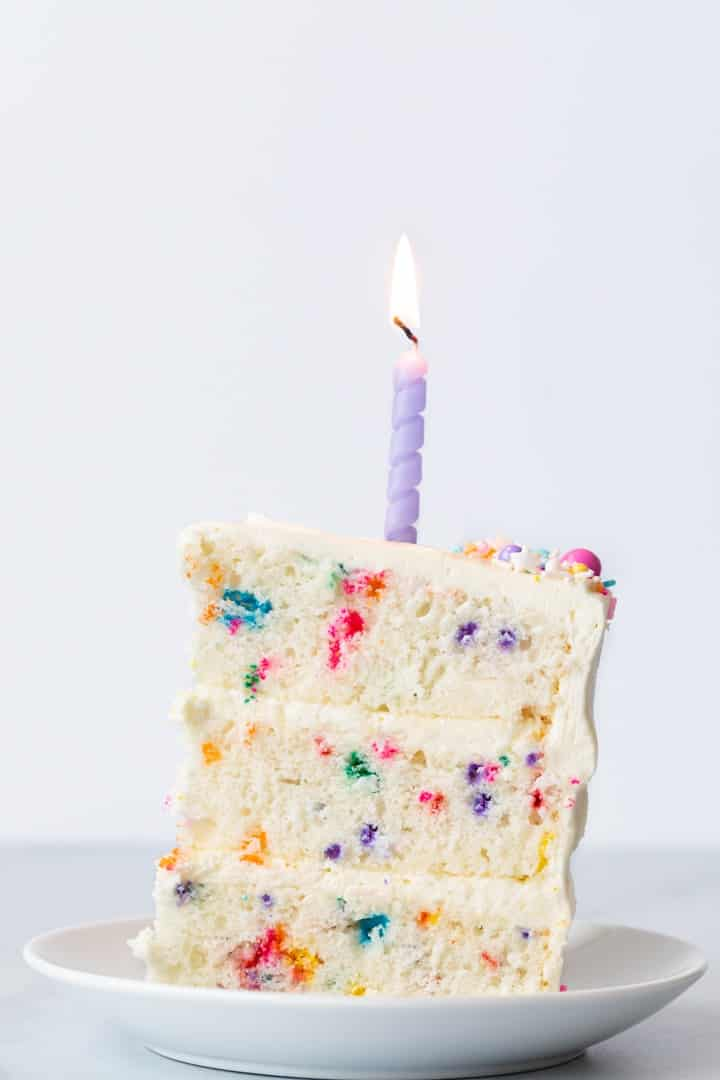 slice of funfetti cake on a white plate with a purple candle on top