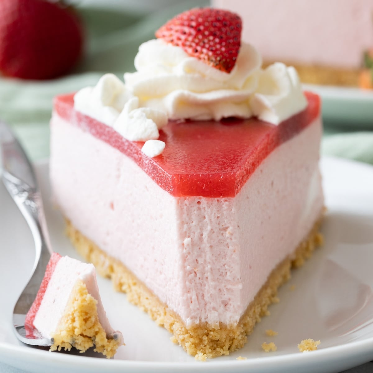 front of a slice of strawberry mousse cake with a fork taking a bite out
