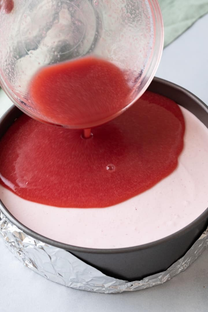 strawberry jam layer being poured over strawberry mousse in a round pan