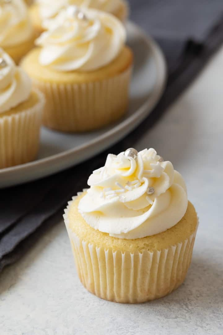 angled view of a vanilla cupcake with vanilla frosting