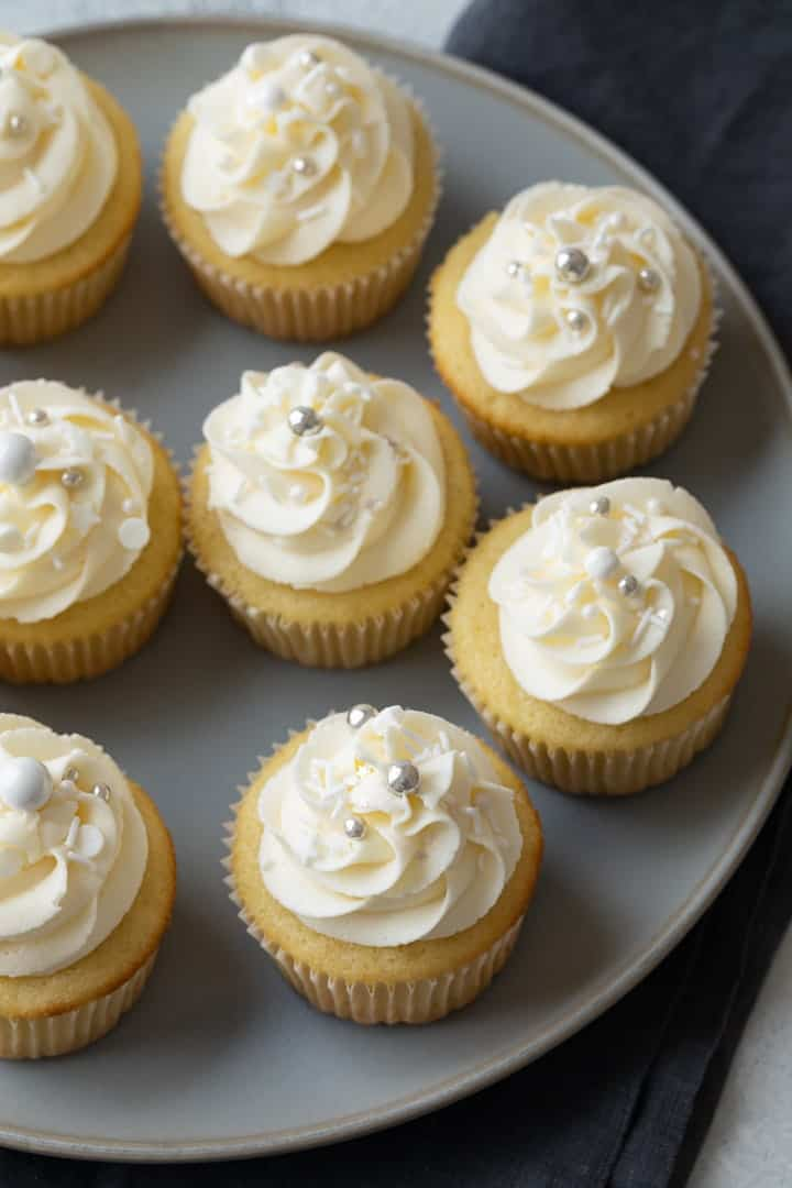 vanilla cupcakes with vanilla frosting on a gray plate