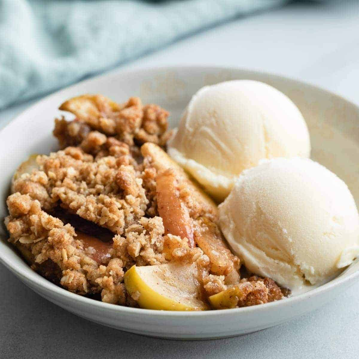 side view of apple crisp in grey bowl with 2 scoops of vanilla ice cream