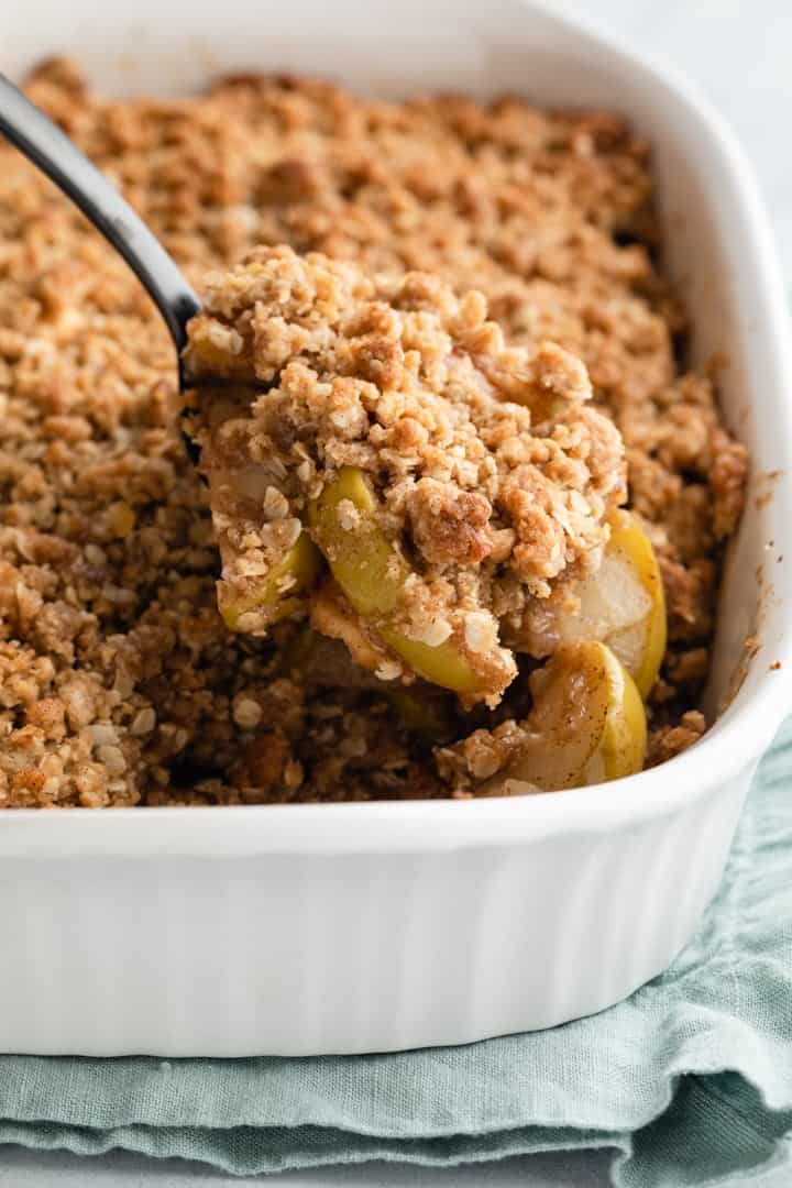 apple crisp being spooned out of a white casserole dish