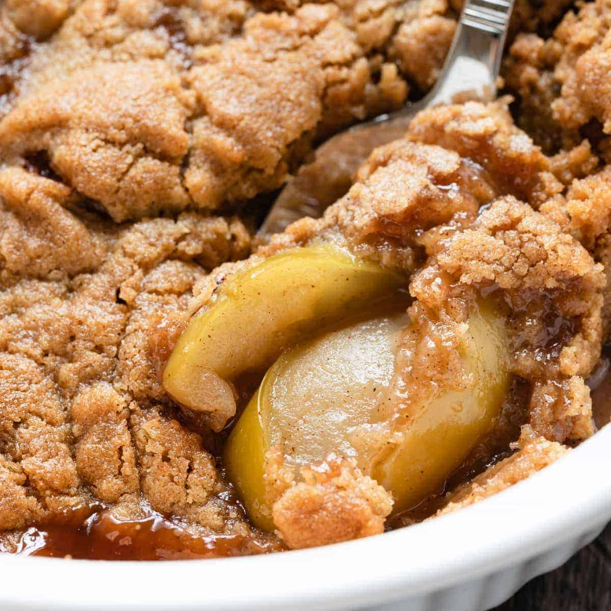 apple crumble in a casserole dish with a spoon scooping some out