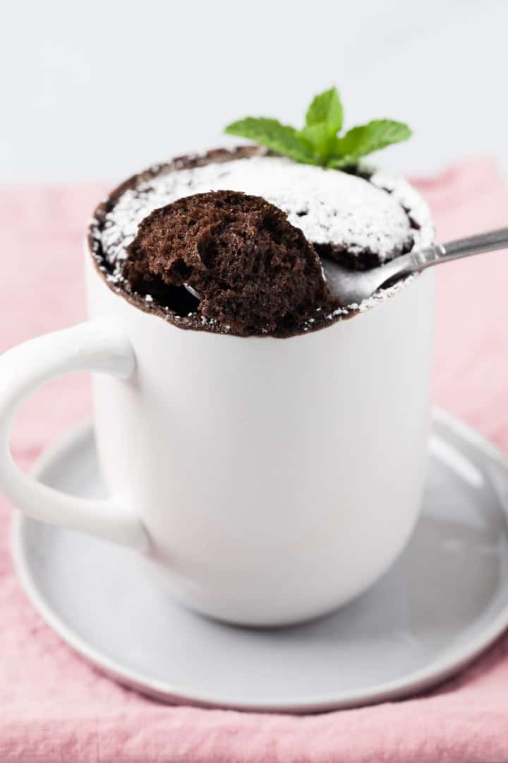a spoon taking a bite out of chocolate mug cake dusted powdered sugar