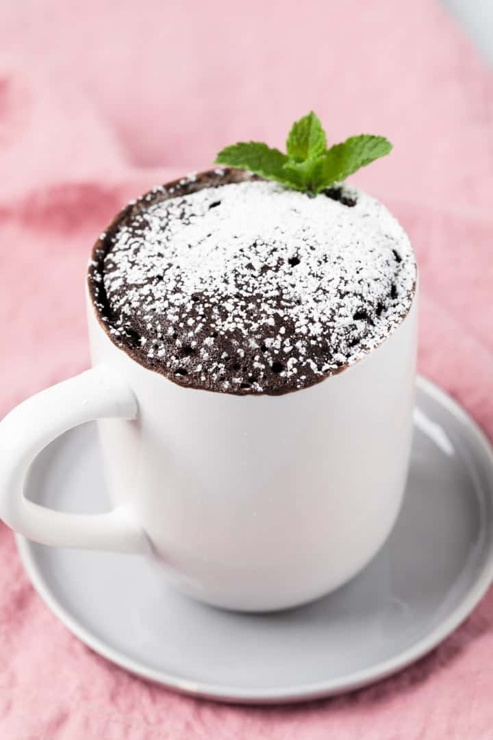 angled view of chocolate mug cake dusted with powdered sugar