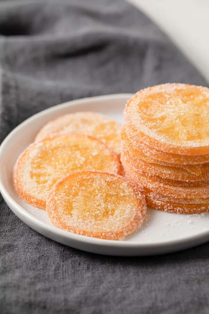candied orange slices on a white plate over a grey napkin