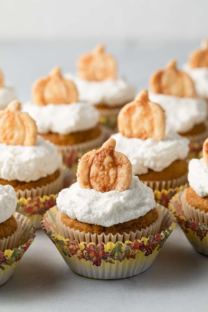 pumpkin cupcakes with whipped cream and pie crust cutouts arranged neatly on a white tabletop