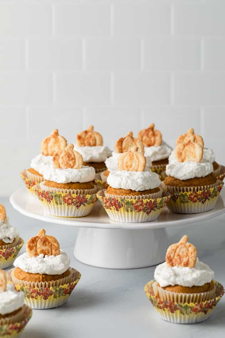 Pumpkin cupcakes with whipped cream frosting and pie crust cutouts on a white cake stand
