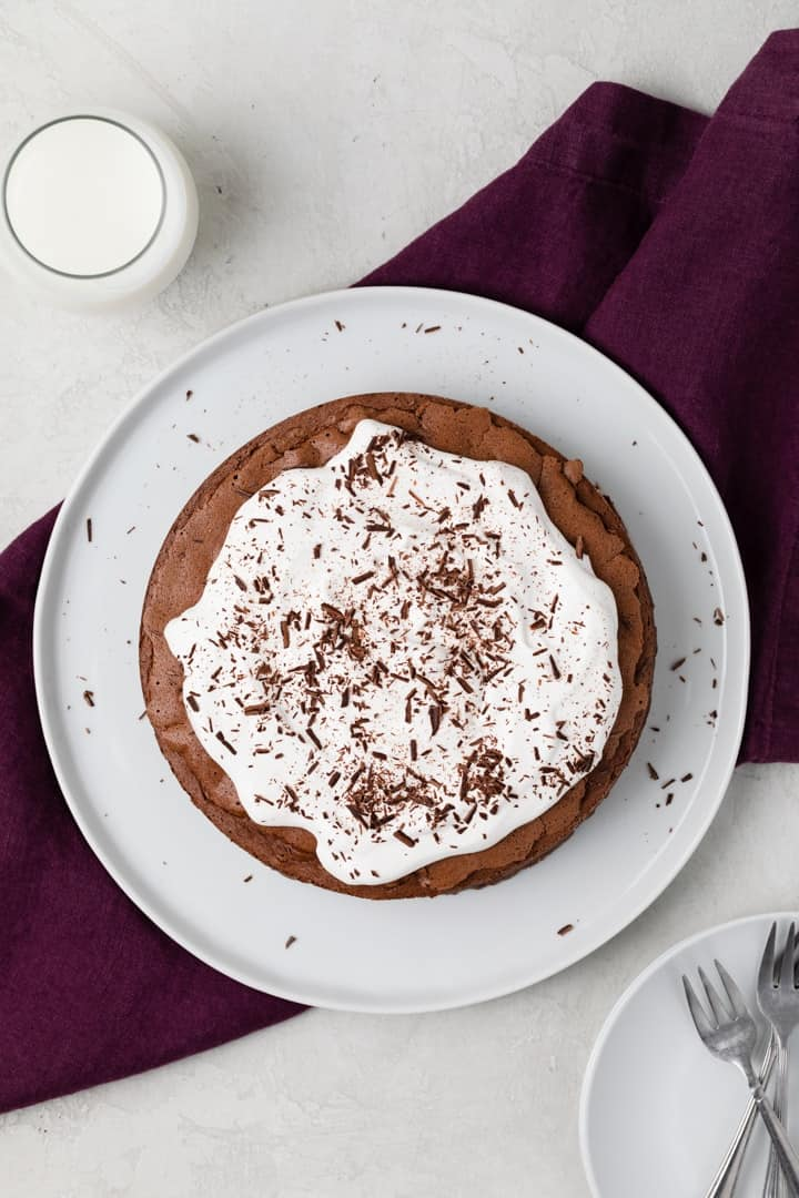 overhead of chocolate cake without flour topped with whipped cream and chocolate shavings