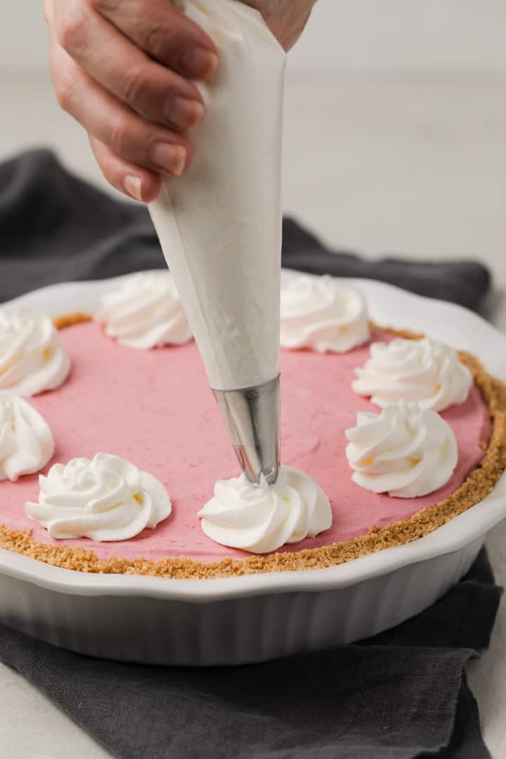 swirls of whipped cream piped on a raspberry pie
