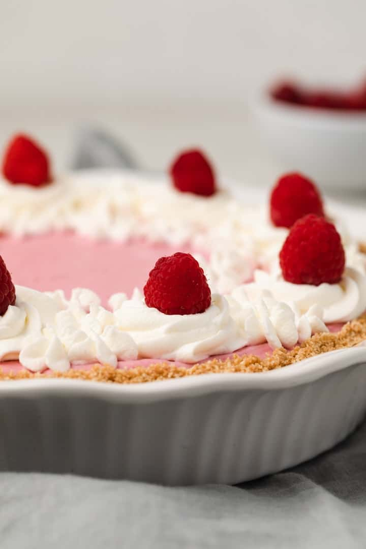 side view of raspberry pie in white pie dish