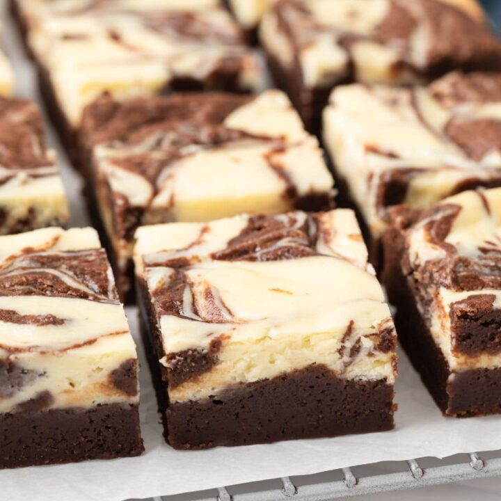 Close up of fudgy cheesecake brownies on a wire rack.