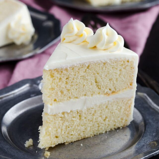 Side view of slice of vanilla cake with vanilla frosting.