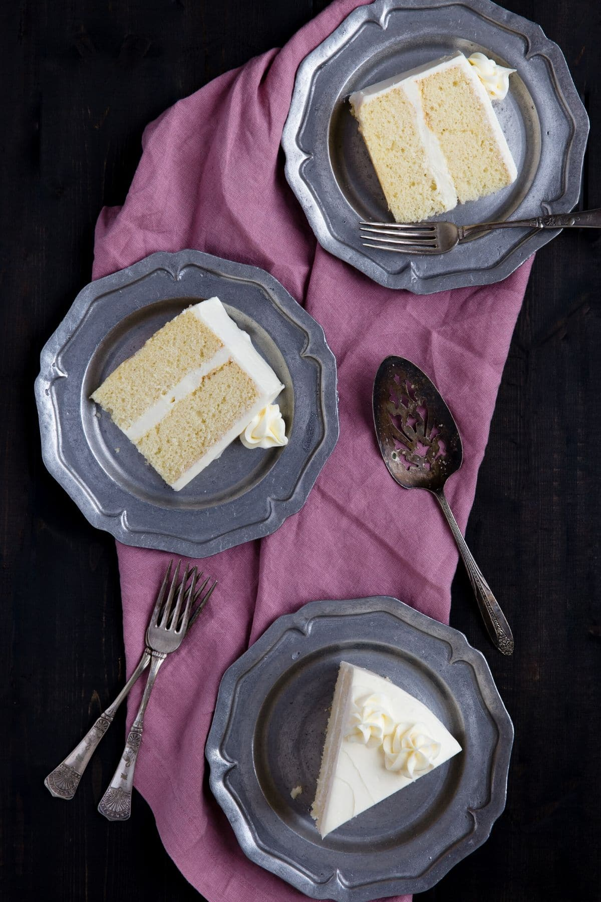 Three pewter plates with a slice of basic vanilla cake on each one.