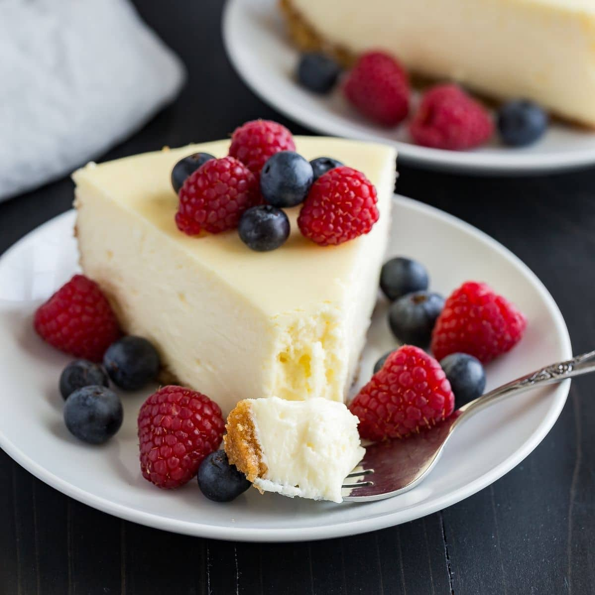 A slice of cheesecake topped with fresh berries and a fork taking out a bite.