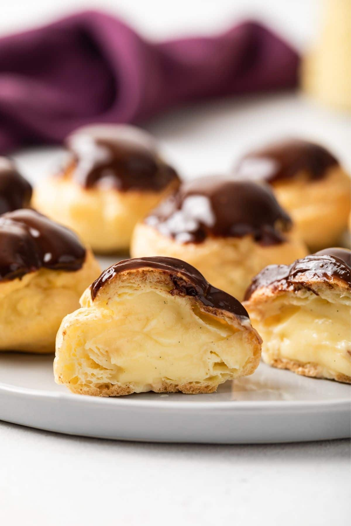 Chocolate glazed profiterole cut open so the filling is visible.