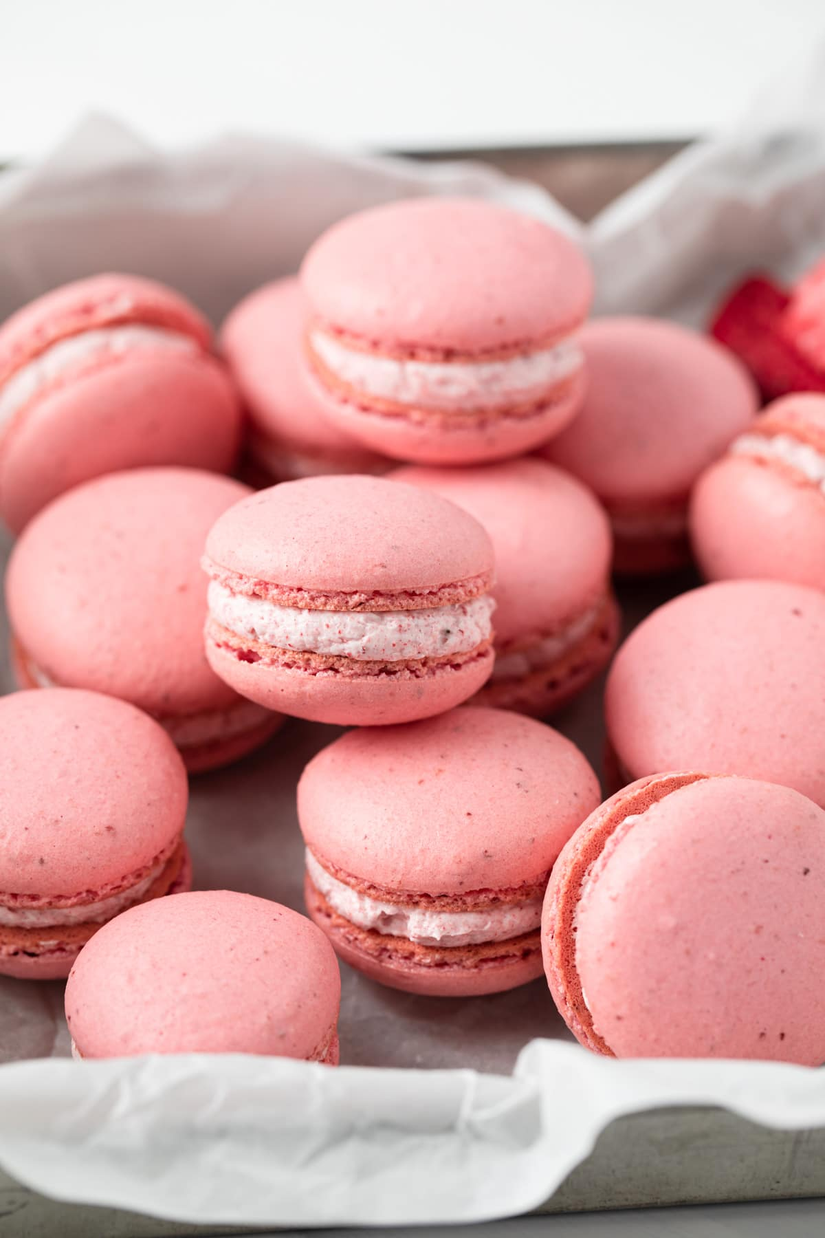 strawberry macarons scattered in a baking sheet liked with parchment paper